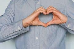 Homme d'affaires faisant un coeur avec ses mains au-dessus du fond blanc, j'aime des affaires Images stock