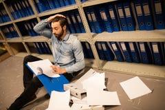 Homme d'affaires fatigué avec les papiers dispersés dans la chambre de stockage de fichier images stock