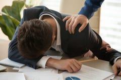 Homme d'affaires fatigué dormant sur le lieu de travail, main masculine le réveillant Photos stock