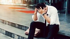 Homme d'affaires fatigué ou soumis à une contrainte sans emploi s'asseyant sur le passage couvert Photo libre de droits