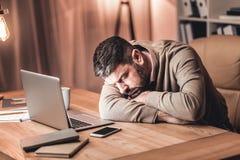Homme d'affaires fatigué s'étendant sur le bureau devant l'ordinateur portable image stock