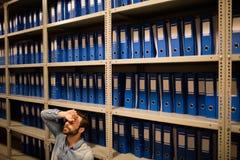 Homme d'affaires fatigué s'asseyant dans la chambre de stockage de fichier photos stock