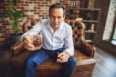 Homme d'affaires fatigué supérieur avec le verre de whiskey Photos stock