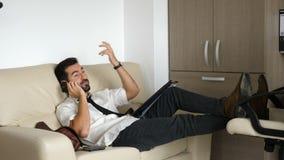 Homme d'affaires fatigué sur le divan parlant au téléphone clips vidéos