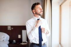 Homme d'affaires fixant son lien dans une chambre d'hôtel Images libres de droits