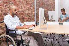 Homme d'affaires focalisé dans le fauteuil roulant fonctionnant à son bureau images libres de droits