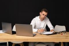 Homme d'affaires focalisé de serios pensant à la tâche en ligne image stock