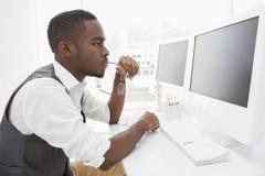 Homme d'affaires focalisé tenant des verres et à l'aide de l'ordinateur images stock