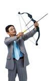 Homme d'affaires focalisé tirant un tir à l'arc photographie stock