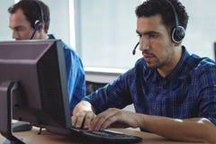 Homme d'affaires focalisé travaillant sur l'ordinateur au centre d'appels photographie stock libre de droits