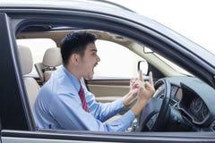 Homme d'affaires fol à l'intérieur d'une voiture Images libres de droits