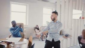 Homme d'affaires fol drôle de danse célébrant la victoire avec les collègues multi-ethniques enthousiastes dans le bureau léger m banque de vidéos