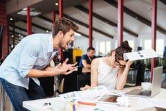 Homme d'affaires fol fol discutant avec la femme d'affaires soumise à une contrainte triste dans le bureau Photographie stock