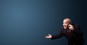 Homme d'affaires fol tenant un téléphone et présent l'espace de copie Photo libre de droits