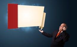 Homme d'affaires fol tenant un téléphone et présent l'origami moderne Image libre de droits