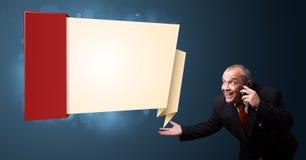 Homme d'affaires fol tenant un téléphone et présent l'origami moderne Photo libre de droits
