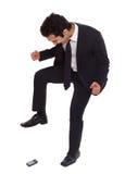 Homme d'affaires frappant du pied sur son phoneq image stock