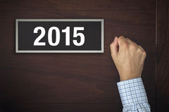 Homme d'affaires frappant sur la porte avec le numéro 2015 Photographie stock libre de droits