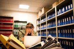 Homme d'affaires frustrant avec la pile des dossiers et de l'ordinateur portable photographie stock libre de droits