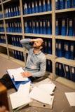 Homme d'affaires frustrant avec le dossier et papiers se reposant dans la salle d'entreposage Photographie stock libre de droits