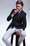 Homme d'affaires fumant sur la chaise grande Photos stock