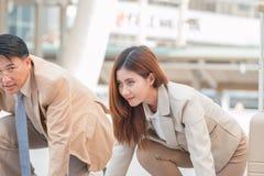 Homme d'affaires futé et femme d'affaires asiatiques se tenant dans le coureur de position de début Images stock