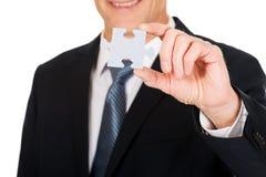 Homme d'affaires futé tenant un puzzle Photographie stock libre de droits