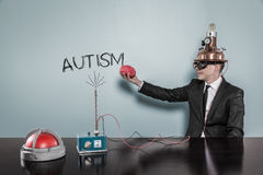 Homme d'affaires In Futuristic Helmet tenant Brain By Autism Text Photos stock