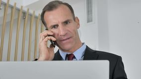 Homme d'affaires ?g? moyen Talking au t?l?phone, ?tant en pourparlers avec le client banque de vidéos