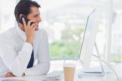 Homme d'affaires gai au téléphone tout en travaillant sur son ordinateur photo stock