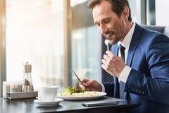 Homme d'affaires gai mangeant de la nourriture dans le restaurant Image stock