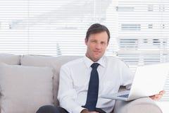 Homme d'affaires gai s'asseyant sur le divan photo libre de droits