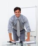Homme d'affaires gai se penchant sur une table de conférence Photo stock