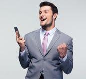 Homme d'affaires gai tenant le smartphone photo stock