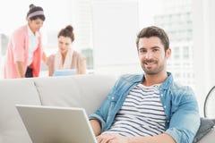 Homme d'affaires gai utilisant l'ordinateur portable sur le sofa photo stock