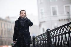 Homme d'affaires gai Walking dans des rues d'hiver Photo stock