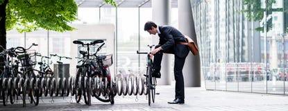 Homme d'affaires garant sa bicyclette en ville Photographie stock