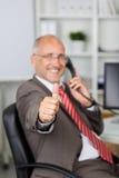 Homme d'affaires Gesturing Thumbs Up tout en à l'aide du téléphone de ligne terrestre photo stock