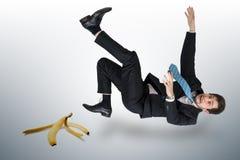 Homme d'affaires glissant sur une peau de banane photos libres de droits
