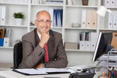 Homme d'affaires With Hand On Chin Sitting At Desk Images libres de droits