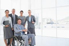 Homme d'affaires handicapé avec ses collègues souriant à l'appareil-photo photographie stock