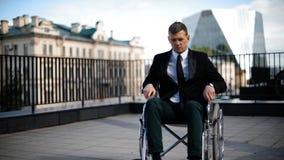 Homme d'affaires handicapé essayant de se lever du fauteuil roulant extérieur banque de vidéos