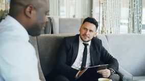 Homme d'affaires d'heure ayant l'entrevue d'emploi avec l'homme d'afro-américain et observant son application de résumé en café m banque de vidéos
