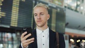 Homme d'affaires heureux à l'aide du smartphone tout en attendant l'embarquement à l'aéroport Le touriste s'attaque par le termin banque de vidéos