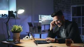 Homme d'affaires heureux appréciant la conversation téléphonique d'affaires dans le bureau foncé banque de vidéos