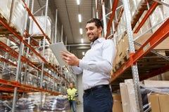Homme d'affaires heureux avec le PC de comprimé à l'entrepôt photos stock