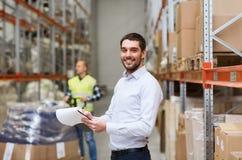Homme d'affaires heureux avec le presse-papiers à l'entrepôt Photos stock