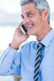 Homme d'affaires heureux ayant un appel téléphonique Photographie stock
