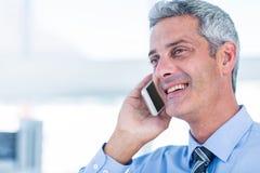 Homme d'affaires heureux ayant un appel téléphonique Photographie stock libre de droits