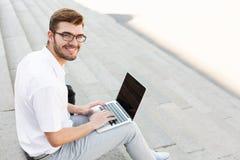 Homme d'affaires heureux bel avec l'ordinateur portable dehors, plan rapproché Photographie stock